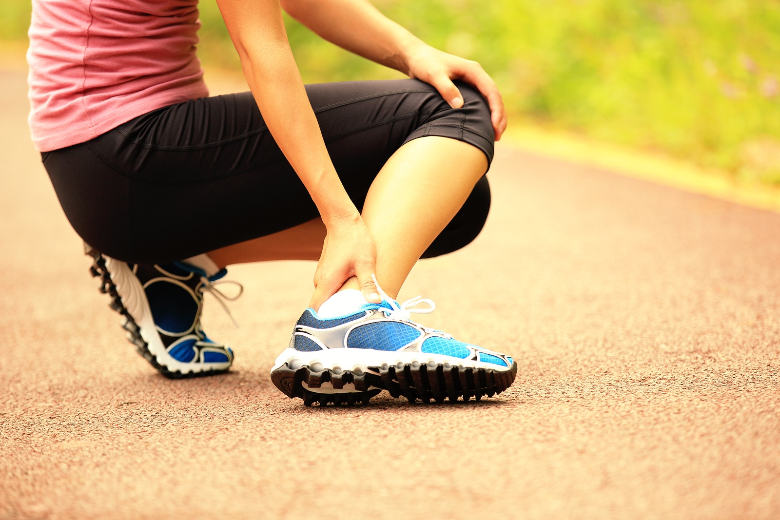 young woman runner hold her twisted ankle ** Note: Shallow depth of field